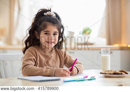 Children Development. Adorable Preschool Arab Girl Drawing In Kitchen At Home
