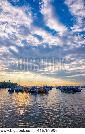 Tourist boats in sea on sunrise in Mumbai, India