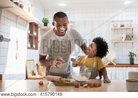 Cheerful Smiling Black Son Enjoying Playing With His Father While Doing Bakery At Home. Playful Afri