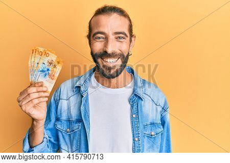 Attractive man with long hair and beard holding 10 swiss franc banknotes looking positive and happy standing and smiling with a confident smile showing teeth