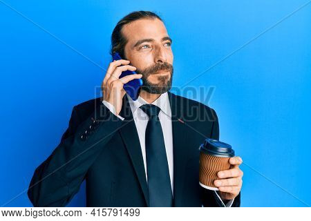 Attractive business man with long hair and beard using smartphone and drinking a cup of coffee smiling looking to the side and staring away thinking.