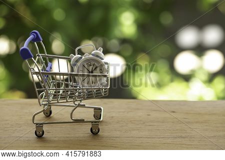 White Analog Clock In A Blue - Silver Shopping Cart Or A Supermarket Shopping Basket On Wooden Table