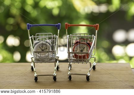 Analog Clock In Silver Shopping Cart Or A Supermarket Shopping Basket On Wooden Table. Fast Delivery