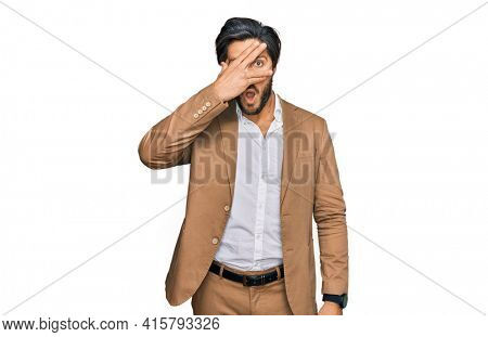 Young hispanic man wearing business clothes peeking in shock covering face and eyes with hand, looking through fingers with embarrassed expression.