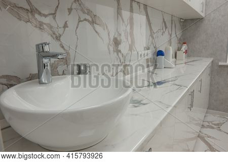 Sink And Countertop In The Cosmetology Room, Cabinets And Marble Tiles