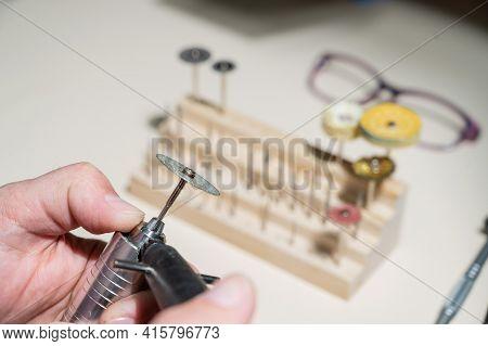 An Optician Technician Polishes The Frame Of Glasses. A Professional Optician Fixes Glasses.