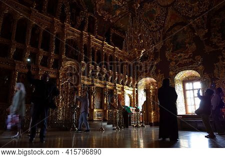 Sergiyev Posad, Russia - June 26, 2019: Tourists at golden decorated interior of Trinity Lavra of St. Sergius monastery. Dark room with natural poor light