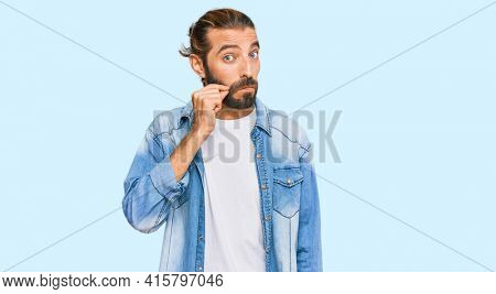Attractive man with long hair and beard wearing casual denim jacket mouth and lips shut as zip with fingers. secret and silent, taboo talking