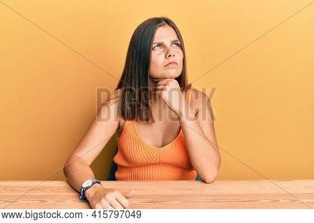 Young caucasian woman wearing casual clothes sitting on the table touching painful neck, sore throat for flu, clod and infection