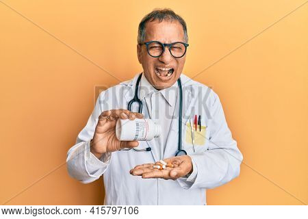 Middle age indian man wearing doctor uniform holding prescription pills smiling and laughing hard out loud because funny crazy joke.