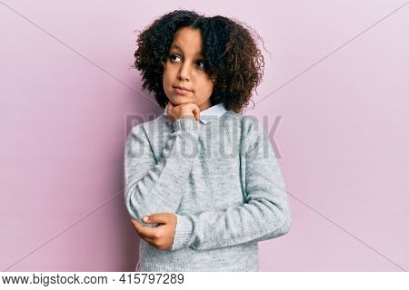 Young little girl with afro hair wearing casual clothes thinking concentrated about doubt with finger on chin and looking up wondering