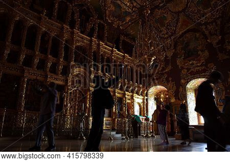 Sergiyev Posad, Russia - June 26, 2019: Tourist at golden decorated interior of Trinity Lavra of St. Sergius monastery. Dark room with natural poor light