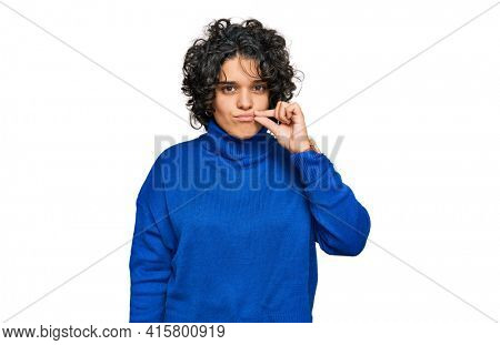 Young hispanic woman with curly hair wearing turtleneck sweater mouth and lips shut as zip with fingers. secret and silent, taboo talking