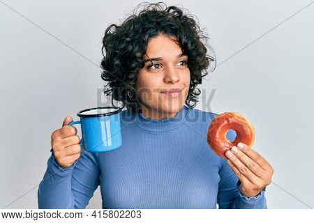 Young hispanic woman with curly hair drinking a cup of coffee and croissant smiling looking to the side and staring away thinking.