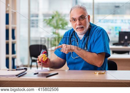 Old male doctor cardiologist working in the clinic