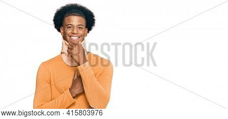African american man with afro hair wearing cervical neck collar looking confident at the camera with smile with crossed arms and hand raised on chin. thinking positive.