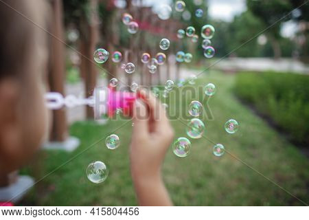 A Little Girl Blowing Soap Bubbles In Summer Park, Happy Childhood, Healthy Outdoors Lifestyle, Ligh