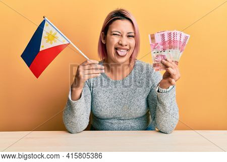 Hispanic woman with pink hair holding philippine flag and philippines pesos banknotes winking looking at the camera with sexy expression, cheerful and happy face.