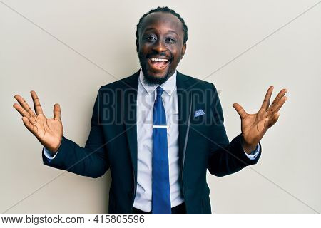 Handsome young black man wearing business suit and tie celebrating victory with happy smile and winner expression with raised hands