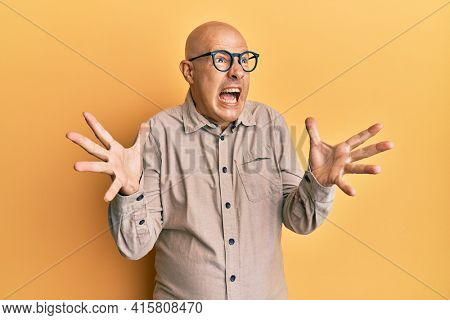 Middle age bald man wearing casual clothes and glasses crazy and mad shouting and yelling with aggressive expression and arms raised. frustration concept.