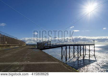 A Walkway On The Shore With A Backlit Jetty.
