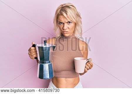 Young blonde girl drinking italian coffee skeptic and nervous, frowning upset because of problem. negative person.