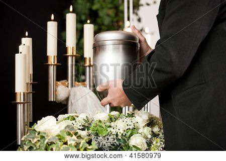 death and dolor  - funeral and cemetery, mortician carrying the urn to a bed of white roses
