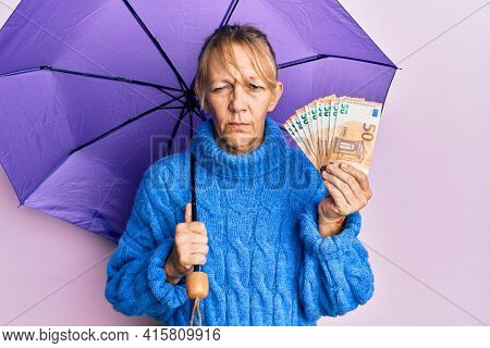 Middle age blonde woman holding umbrella and 50 euros banknotes skeptic and nervous, frowning upset because of problem. negative person.