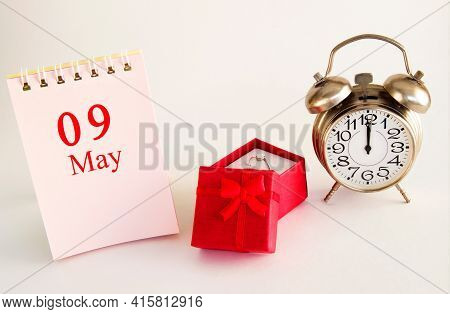 Calendar Date On Light Background With Red Gift Box With Ring And Alarm Clock With Copy Space. May 9