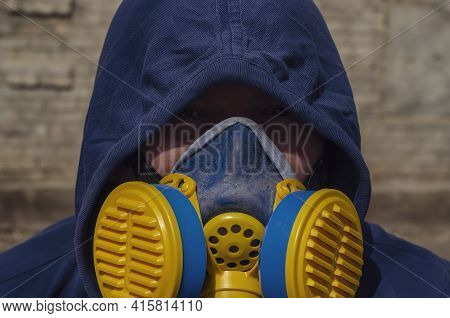 Portrait Of An Adult Unrecognizable Man Wearing A Respirator And Hood On Against A Brick Wall. Middl