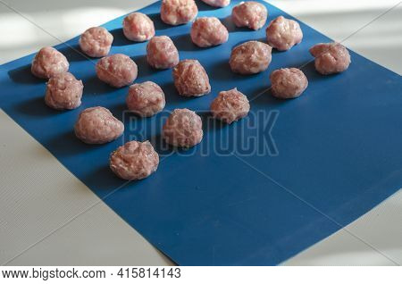 Raw Shaped Meatballs On Blue. Rows Of Meatballs With Pepper, Salt And Spices. Side View At An Angle.
