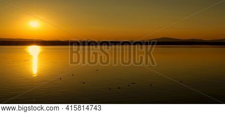 Vacation sea sunset landscape.Sea water surface lit by sunset light,summer vacation water scene,sea summer vacation nature with mountains at the horizon, summer vacation panoramic view,sea summer vacation concept