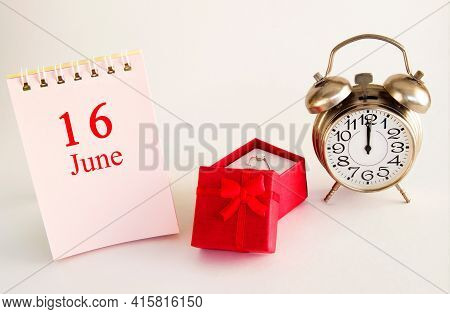 Calendar Date On Light Background With Red Gift Box With Ring And Alarm Clock With Copy Space. June