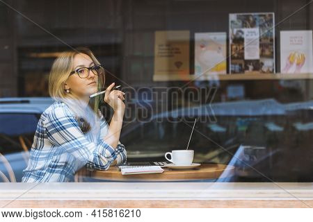 Young Beautiful Woman Working In A Cafe And Thinking. Online Courses. Freelance, New Normal Working.