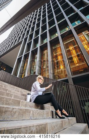 White Collar Businesswoman Working With Coffee And Laptop On The Steps Of A High-rise Building. Succ