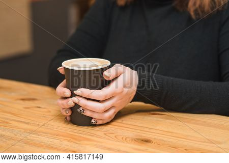 Photo With Female Hands Holding A Glass Of Coffee In The Cafeteria