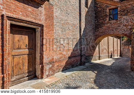 Wooden door and brick wall of old house on narrow cobblestone street in town of Guarene, Piedmont, Northern Italy.