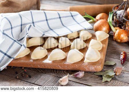 The Process Of Making Home-made Dumplings. Raw Homemade Dumplings On A Wooden Board. Molding Dumplin