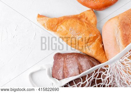 Bakery Products In Mesh Bag On The White Table. Puff Pastry Khachapuri, Yeast-free Rye Bread And Whi