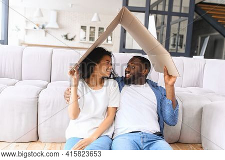 Portrait Of African Young Happy Couple Sitting On The Couch Holding Cardboard Board In The Form Of R