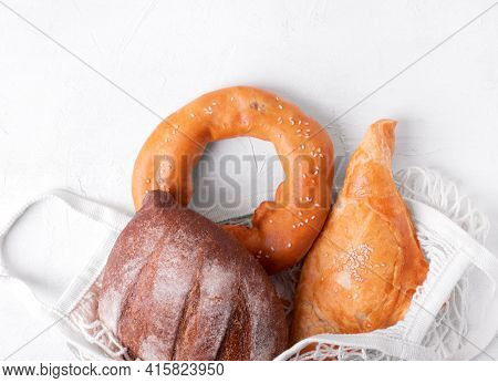 Bakery Products In Mesh Bag On The White Table. Puff Pastry Khachapuri , Bagel And Yeast-free Rye Br