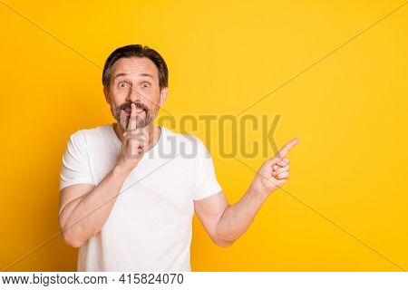 Photo Of Shocked Mature Man Hold Finger Lips Silence Point Finger Empty Space Isolated On Yellow Col