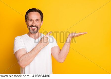 Photo Of Happy Cheerful Mature Man Point Finger Hold Hand Empty Space Advert Isolated On Yellow Colo