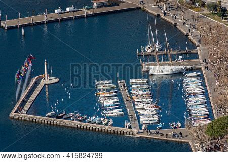 Aerial View Of The Port Of The Small Garda Town, Tourist Resort On The Coast Of Lake Garda, View Fro