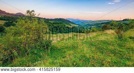 Mountainous Rural Landscape At Dawn. Beautiful Scenery With Forests, Hills And Meadows In Morning Li