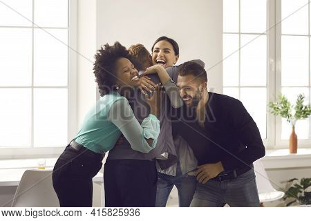 Group Of Young People Hugging Friend Congratulating Him On Promotion Or Happy Life Event