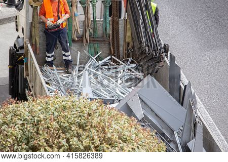 Worker Operating A Crane Loading A Truck With Metallic Scrap. Metal Recycling