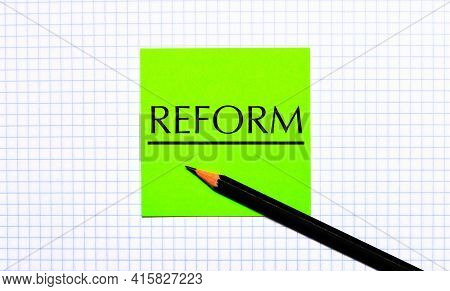 There Is A Green Sticker With The Text Reform And A Black Pencil On The Checkered Paper.