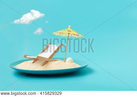 Tropical Beach Concept Made Of Plate With Sand, Deck Chair And Sun Umbrella. Creative Summer Vacatio