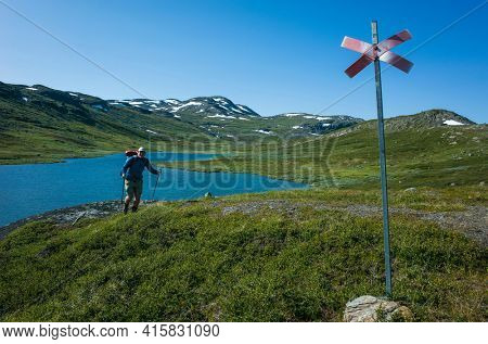 Hiking in Swedish Lapland. Man traveler trekking alone with view of mountain lake Allagasjavri in northern Sweden. Arctic nature of Scandinavia in warm summer sunny day with blue sky